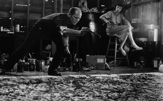 Jackson Pollock at work on One, 1950, with Lee Krasner in the background.